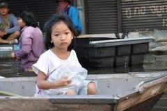 一个哀伤的liggle女孩是在小船,看在曼谷一条被充斥的街道的照相机,泰国, 2011年11月06日 免版税图库摄影