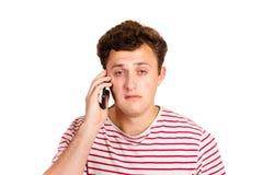 一个哭泣的人在他的电话读一个正文消息 与坏消息的Sms 在白色背景隔绝的情感人 图库摄影
