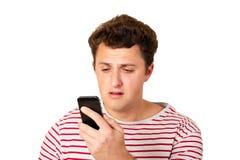 一个哭泣的人在他的电话读一个正文消息 与坏消息的Sms 在白色背景隔绝的情感人 库存图片
