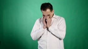 一个哭泣的人的特写镜头画象 一个年轻商人闭上他与泪花的酸疼的眼睛在绿色背景 影视素材