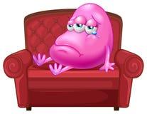 一个哭泣的妖怪坐一个红色沙发 免版税图库摄影
