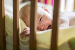 一个哭泣的逗人喜爱的婴孩的特写镜头画象小儿床的在家 免版税库存图片