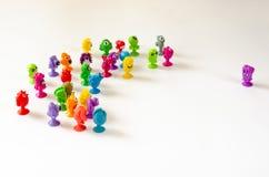 一个唯一字符面对一个小组图 在白色背景的五颜六色的橡胶妖怪小雕象 图库摄影