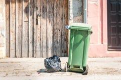 一个唯一绿色垃圾箱和黑塑料破烂物在城市等待的倾销者卡车的街道上请求收集在前面 库存图片