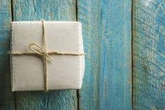 一个唯一节日礼物箱子的顶上的看法栓与在一张土气木桌上的麻线 免版税图库摄影