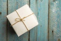 一个唯一节日礼物箱子的顶上的看法栓与在一张土气木桌上的麻线 库存图片