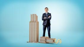 一个商人用手在上面横渡了在一个小打破的企业大厦上的身分与一USD签字 库存照片