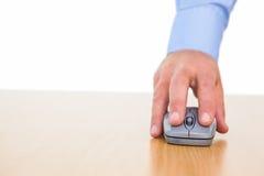 一个商人的手使用老鼠的在书桌 免版税库存照片