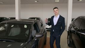一个商人的画象在一套衣服的在有钥匙的陈列室里的新的汽车 影视素材
