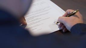 一个商人的背面图在黑衬衣签署的合同的 股票 把他的署名放的人在重要文件上 股票录像