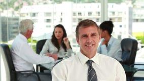 一个商人的画象与同事的在会议在背景中 股票视频