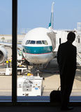 一个商人等待的搭乘的剪影在机场 免版税库存照片