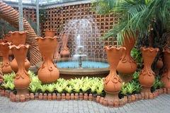 一个喷泉和罐在芭达亚市附近的Nong Nooch热带植物园里在泰国 免版税库存照片
