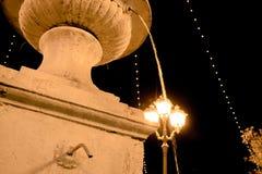 一个喷泉在与下来的水和一盏灯的光的晚上在街道的 图库摄影