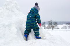一个四岁的孩子,男孩,攀登多雪的小山 库存图片
