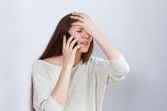 一个困厄的少妇的画象谈话在电话 免版税库存图片