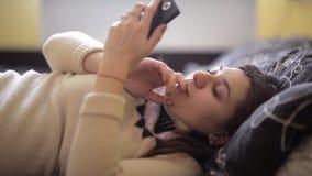一个困女孩在床上说谎并且使用智能手机 股票录像