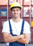 一个国外容器的笑的码头工人infront 图库摄影