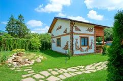 一个土气样式的两层乡间别墅在夏天庭院里站立 图库摄影