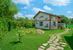 一个土气样式的两层乡间别墅在夏天庭院里站立 免版税库存照片