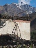 一个土气西藏房子:白色墙壁,在屋顶的一把刷子,与祷告的色的佛教旗子,石篱芭,在Himal的夏天 图库摄影