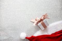 一个圣诞老人帽子和一个小礼物盒在银色闪烁backgro 图库摄影