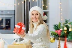 一个圣诞老人帽子的一个女孩有一件礼物的在她的手上Christma的 库存照片