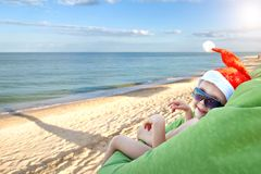 一个圣诞老人帽子的一个小孩子在海滩庆祝圣诞快乐 图库摄影