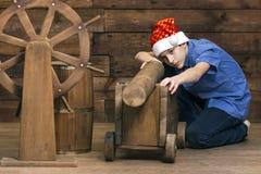 一个圣诞老人帽子的一个少年有在他的面孔的一个严肃的表示的在桶和指点wh附近建议枪大模型 图库摄影