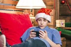 一个圣诞老人帽子的一个少年,在牛仔裤,在一件蓝色衬衣,在与红色枕头的一把椅子说谎并且看在wal的电话 库存图片