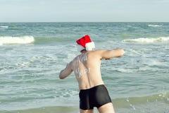一个圣诞老人帽子的人与在他的后面div的题字新年 图库摄影