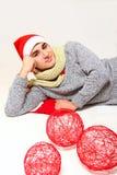 一个圣诞老人帽子的年轻人有在白色查出的红色球的 免版税库存照片
