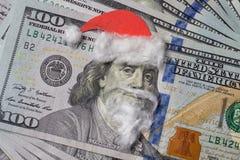 一个圣诞老人帽子的本杰明・富兰克林有在票据的胡子的 图库摄影
