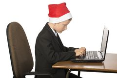 一个圣诞老人帽子的男孩在计算机 库存照片