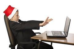一个圣诞老人帽子的男孩在计算机 免版税库存图片