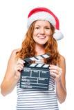 一个圣诞老人帽子的美丽的女孩有在白色的一个电影拍板的 免版税库存图片