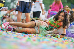一个在最滑稽和最五颜六色的都市赛跑的疲乏的参加者休息,颜色奔跑 库存照片