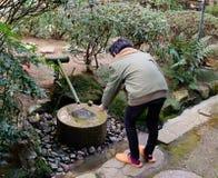 一个在来的人洗涤的手到寺庙前在东京,日本 库存图片