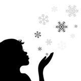 一个在白色背景隔绝的小女孩吹的雪花的剪影 向量EPS8 图库摄影