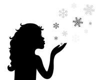 一个在白色背景隔绝的小女孩吹的雪花的剪影 免版税库存图片