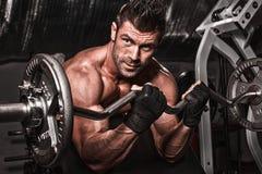 一个在黑暗的backgrou的肌肉年轻人举的重量的特写镜头 免版税图库摄影