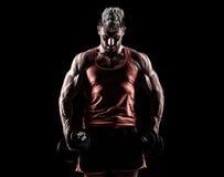 一个在黑暗的backgrou的肌肉年轻人举的重量的特写镜头 图库摄影