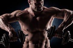 一个在黑暗的backgrou的肌肉年轻人举的重量的特写镜头 免版税库存图片