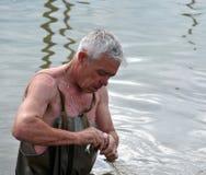 一个地方人钓鱼与网在一次洪水期间在庭院里 图库摄影