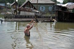 一个地方人钓鱼与网在一次洪水期间在庭院里 库存照片