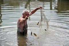 一个地方人钓鱼与网在一次洪水期间在庭院里 免版税图库摄影