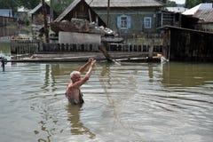 一个地方人钓鱼与网在一次洪水期间在庭院里 免版税库存照片