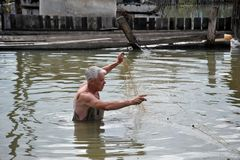 一个地方人钓鱼与网在一次洪水期间在庭院里 库存图片