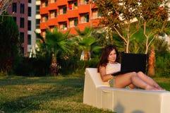 一个地毯的女孩与在日落的一台膝上型计算机 免版税库存图片