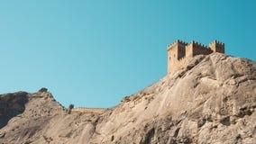 一个坚固的堡垒高在峭壁,点燃由明亮的太阳 图库摄影